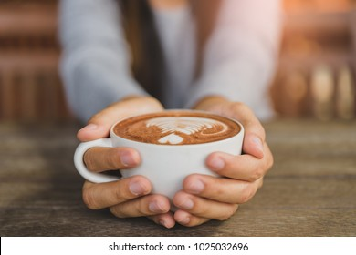 Woman hands holding cup of hot coffee latte cappuccino with heart shaped. Love, Wedding and Valentines day concept.