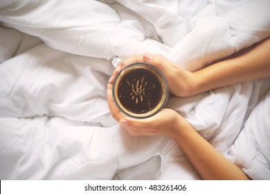 Woman hands holding a cup of hot coffee in bed, top view