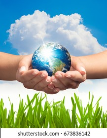Woman hands holding earth in front of cloudy blue sky and green grass. Save the earth concept.