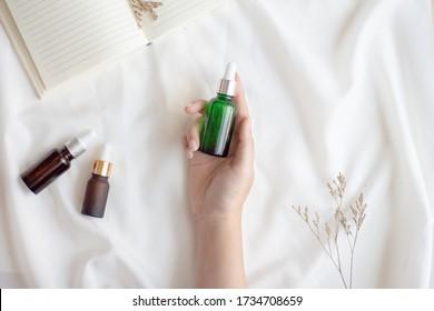 Les mains de la femme tenant de l'huile essentielle du visage ou des emballages de sérum sur fond de tissu blanc. Produit cosmétique de beauté pour le concept de soins de la peau. Vue supérieure, minimale. Douce et lisse.