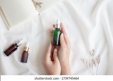 Les mains de la femme tenant de l'huile essentielle du visage ou des emballages de sérum sur fond de tissu blanc. Produit cosmétique de beauté pour le concept de soins de la peau. plan plat Vue supérieure.