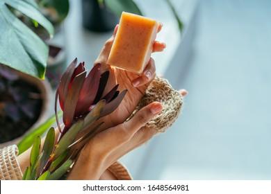 Weibliche Hände, die Blumen und natürliche organische grüne Seifenbar halten, die mit Olivenöl auf dem Hintergrund der grünen Bade-Pflanzen im Inneren hergestellt wird. Gesunder Lebensstil, Schönheit, Hautpflege. Zero-Müll-Home-Konzept.