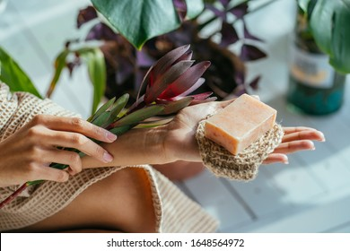 Woman hands holding flower and organic soap and jute washcloth in the woman's hand. on bath interior green plants background. Healthy lifestyle, beauty, skin care. Zero waste, home concept.