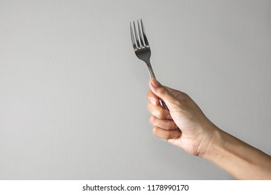 Woman hands holding a fork.
