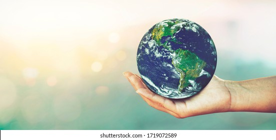 Woman hands holding global over blurred nature backgrounds, Concept of Love the World.Elements of this image furnished by NASA.