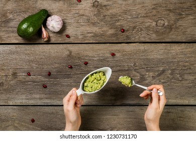 Woman hands holding gravy boat and tea spoon with guacamole sauce on wooden background