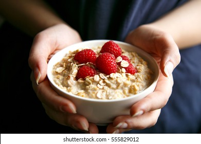 Woman hands holding healthy and natural breakfast, oatmeal and raspberries in a bowl