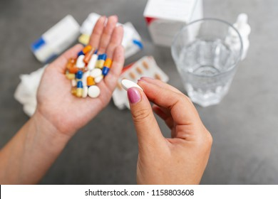 Woman hands holding heap of small round meds with glass of water before taking medication