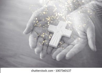 Woman hands holding a holy cross on wooden table.black and white tone.