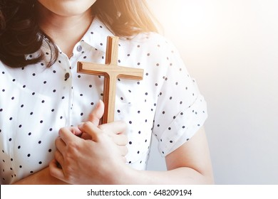 Woman hands holding a holy cross near heart , Praying for God Religion