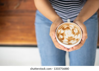 woman hands holding hot coffee up.Close up coffee cup in hands.
