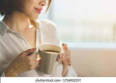 Woman hands holding hot cup of coffee or tea in morning sunlight.