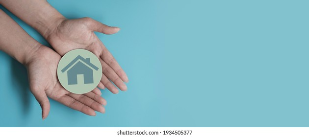 Woman hands holding house icon with paper cut, family home, homeless shelter, international day of families, foster home care, family day care, social distancing, stay at home, housing mortgage crisis