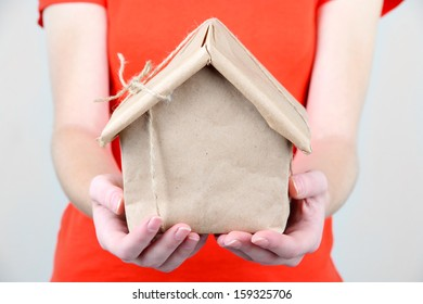Woman hands holding a house wrapped in brown kraft paper