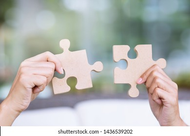 Woman hands holding joining pieces connecting jigsaw puzzle help in business solutions teamwork and help concept