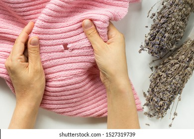 Woman hands holding the knitted thing with hole made by moth and bunch of lavender