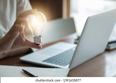 woman hands holding light bulb in working place.