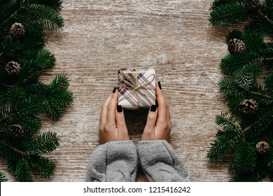 Woman hands holding little present box  on the wooden background with  spruce branches