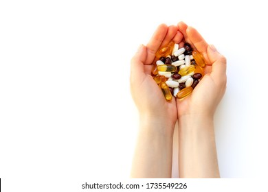 Woman hands holding a lots of pills or vitamins, isolated on white background.
