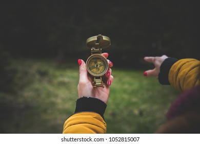 Woman hands holding a magnetic compass in nature.