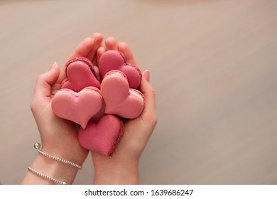 Woman hands holding many pink macaroons in the heart shape