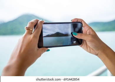 woman hands holding mobile phone at Sea and mountains