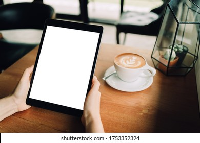 A woman hands are holding a mockup of black tablet with blank white screen   in the cafe with a white cup of latte coffee. sitting on the wood table, clipping path included