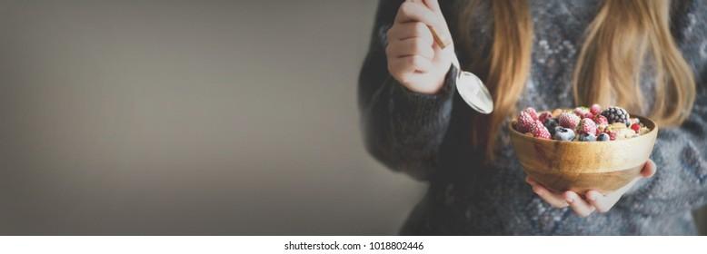 Woman hands holding oatmeal porridge with frozen berries, almonds in wooden bowl. Banner. Healthy breakfast. Clean eating, detox diet. Vegetarian, raw, vegan concept
