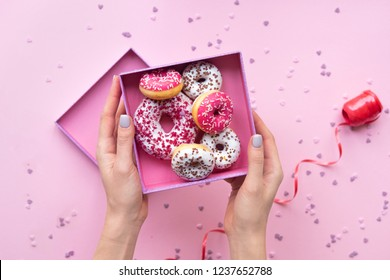 Woman hands holding  open box with colorful donuts on pink background.