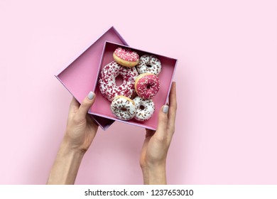 Woman hands holding  open box with donuts on pink background. Flat lay style. Copy space.