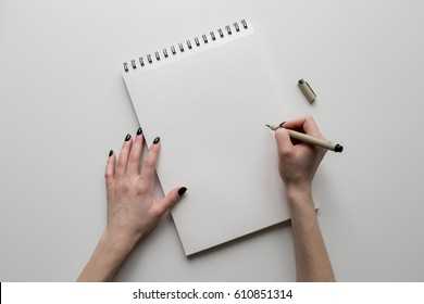 Woman hands holding paper sheet or notebook and pen. White table. Top view