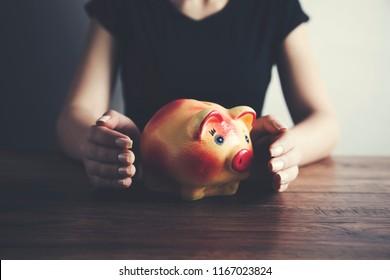 Woman hands holding piggy bank