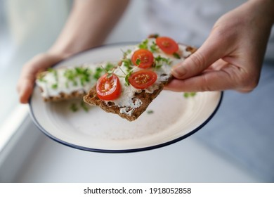 Woman hands holding plate with rye crisp bread with creamy vegetarian cheese tofu, cherry tomato and rucola micro greens. Healthy food, gluten free, diet concept.