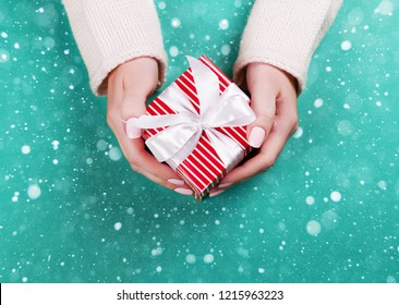 Woman hands holding present box with red bow on pastel green background. Flat lay style.