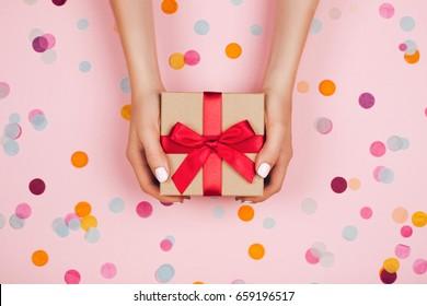 Nainen kädet tilalla läsnä laatikko punainen keula pastelli vaaleanpunainen tausta monivärinen konfetti. Litteä makasi tyyli.