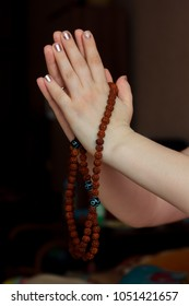 Woman hands holding rudraksha rosary with the namaste mudra.