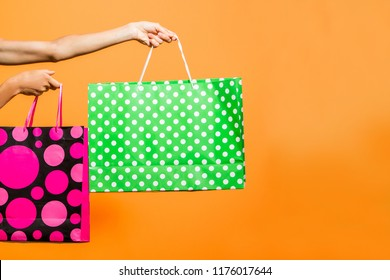 Woman hands holding shopping bags over bright background, minimal style