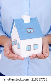 Woman hands holding small house close up