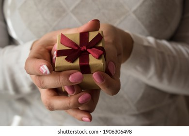 Woman hands holding a small present box with red ribbon over. Valentine gift box. Close up shot of female hands.Shallow depth of field with focus on the little box.