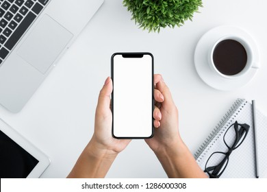 Woman hands holding smartphone with blank white screen in office, top view, copy space