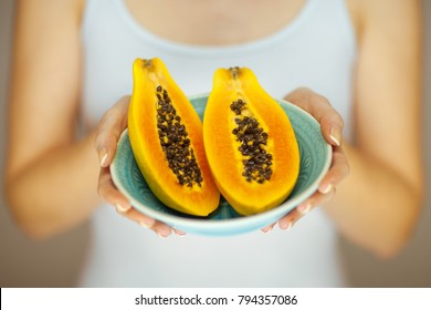 woman hands holding some papayas, sensual studio shot can be used as background
