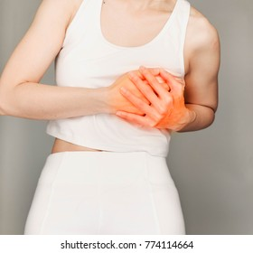 Woman with hands holding to spot of her chest in pain, heart disease.  Health-care Concept.Selective focus