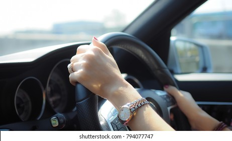 Woman hands holding a steering wheel confidently. (Selected focus)