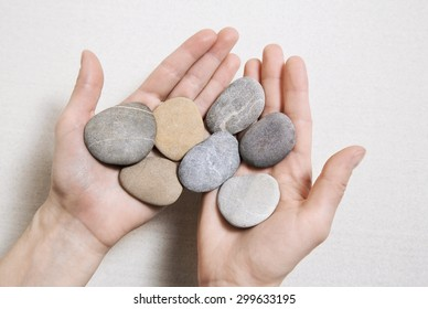 Woman hands holding stones. Concept for balance, combination, life, teamwork and so on.