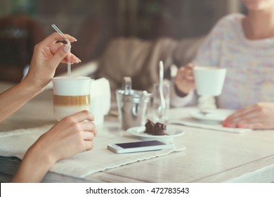 Woman hands holding straw in glass of latte
