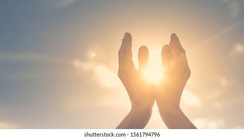 Woman hands holding the sun at dawn. Freedom and spirituality concept.  - Shutterstock ID 1561794796