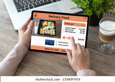 woman hands holding tablet computer with app delivery food on the screen in office