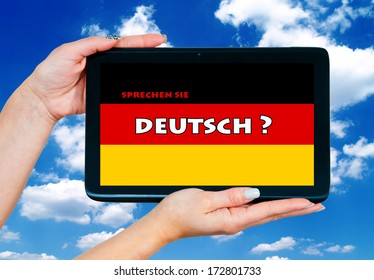 woman hands holding tablet with german language learning sign on the screen and blue sky in background