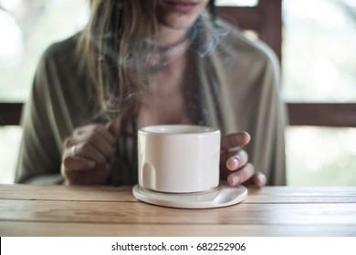 woman hands holding a white mug with steam