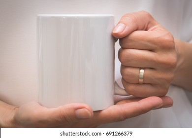 Woman hands holding white mug